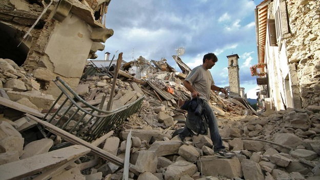 倒壊した住宅の上を足早に横切るイタリア人男性
