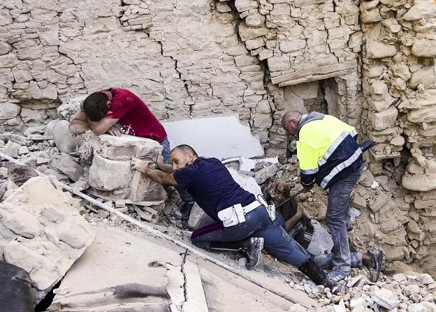 瓦礫と化した建物の上で泣き崩れるイタリア人男性