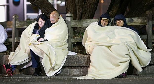 ニュージーランド地震の被災者が野外で毛布に包まって寒さをしのぐ写真