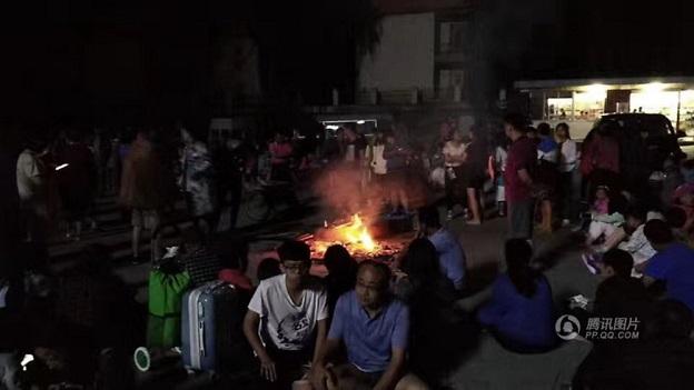 九寨溝地震で被災した旅行者達は焚火で暖をとっている。九寨溝は高山地帯なので夜は夏でも気温10度付近まで冷え込む